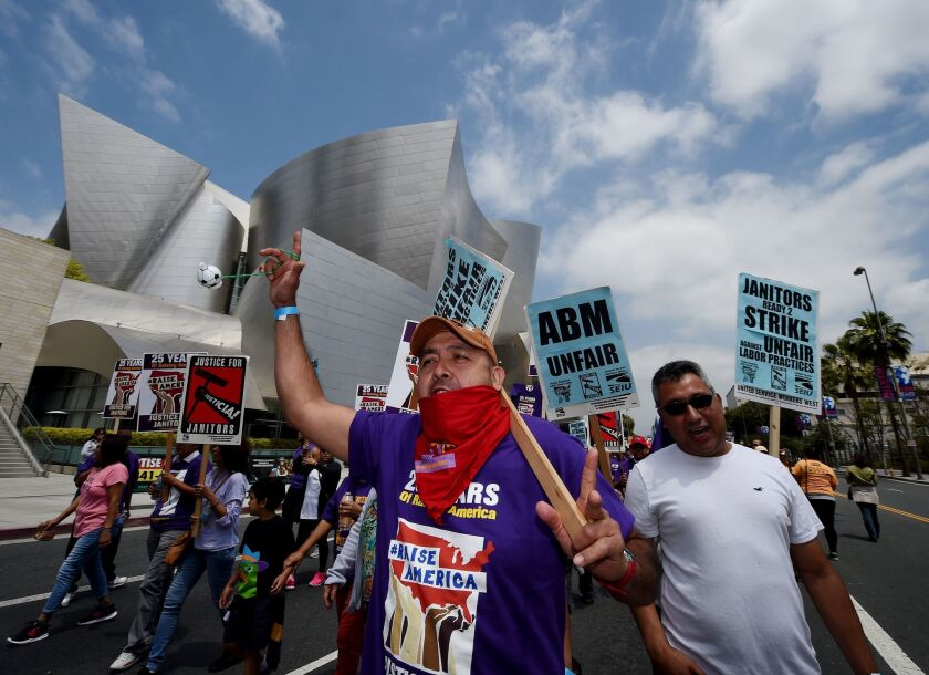 A group of janitors estimated by police to number 3,000 marches through downtown Los Angeles on April 29, 2016, as they demonstrate over wages and threaten to strike.