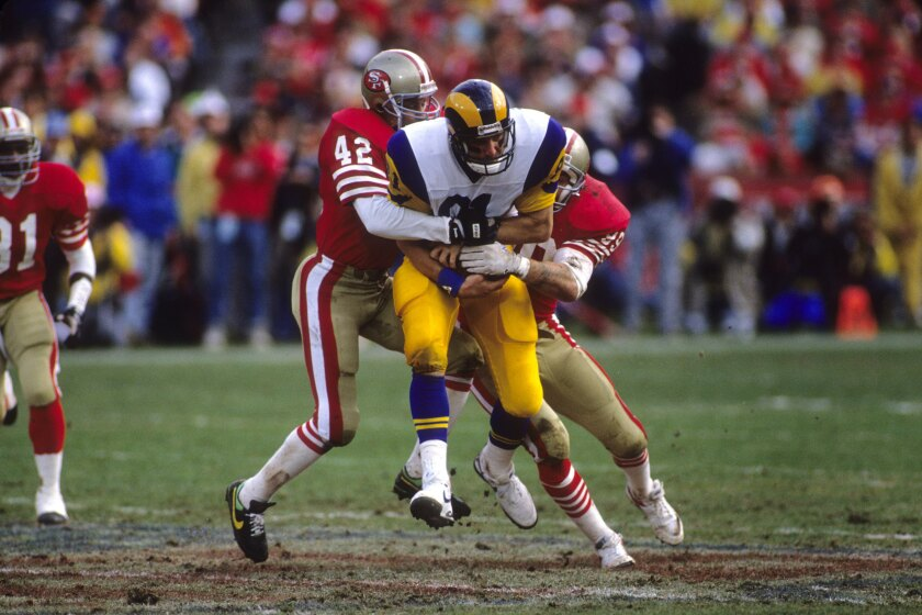 Rams tight end Pete Holohan is brought down by 49ers safety Ronnie Lott (42) and linebacker Michael Walter during the NFC championship game after the 1989 season.