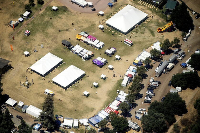 FILE - In this July 29, 2019 aerial file photo, vendor booths line Christmas Hill Park in Gilroy, Calif., the site of a shooting the day before, at the Gilroy Garlic Festival. A lawsuit announced Tuesday, Nov. 12, 2019, against the Gilroy Garlic Festival Association alleges that negligent security measures allowed a gunman to sneak in and fatally shoot three people. (AP Photo/Noah Berger, File)