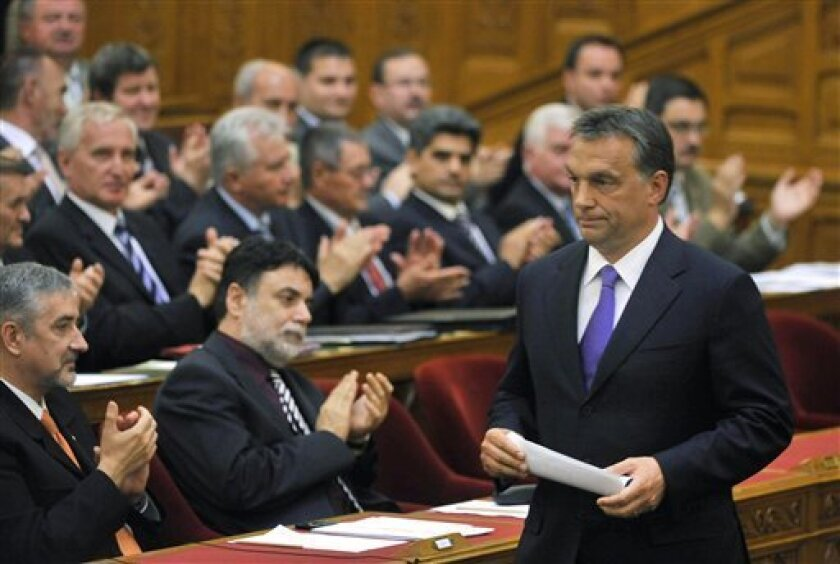 Hungarian Prime Minister Viktor Orban passes parliamentarians after announcing his government's new economic rescue package programme during the plenary session of the lawmakers in the parliament building in Budapest, Hungary, Tuesday, June 8, 2010. (AP Photos/MTI, Zsolt Szigetvary)