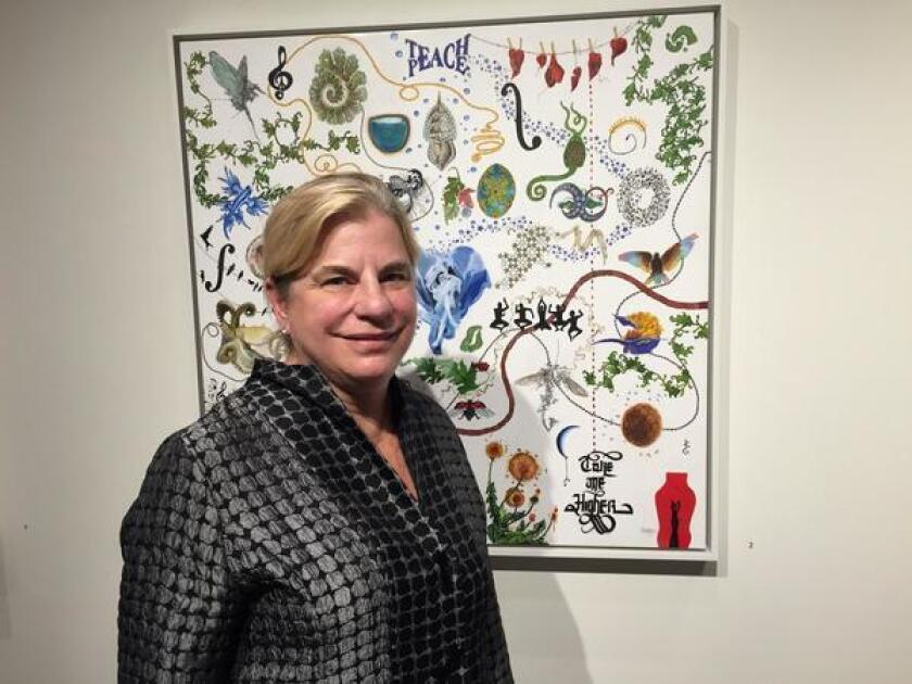 In Lux's Education Pavilion, executive director Kathleen Stoughton poses with one of Becky Robbins' paintings, on view through Oct. 6. Robbins won first place in La Jolla Athenaeum's Juried Art Exhibition this year.