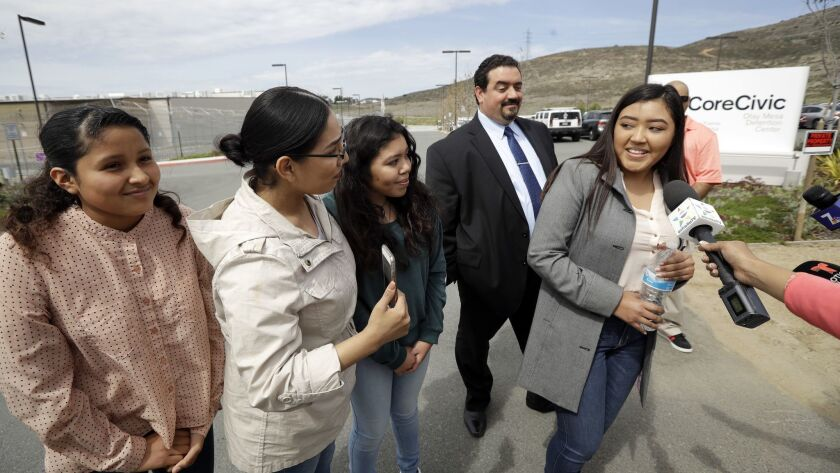 Yessica Estrada, right, a daughter of Perla Morales Luna, looks back at friends and family members a