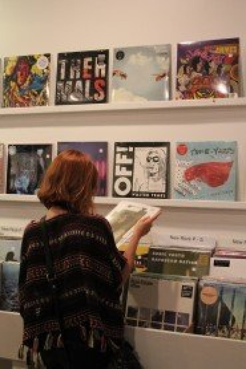 a customer examines a record jacket at M-Theory's grand opening party