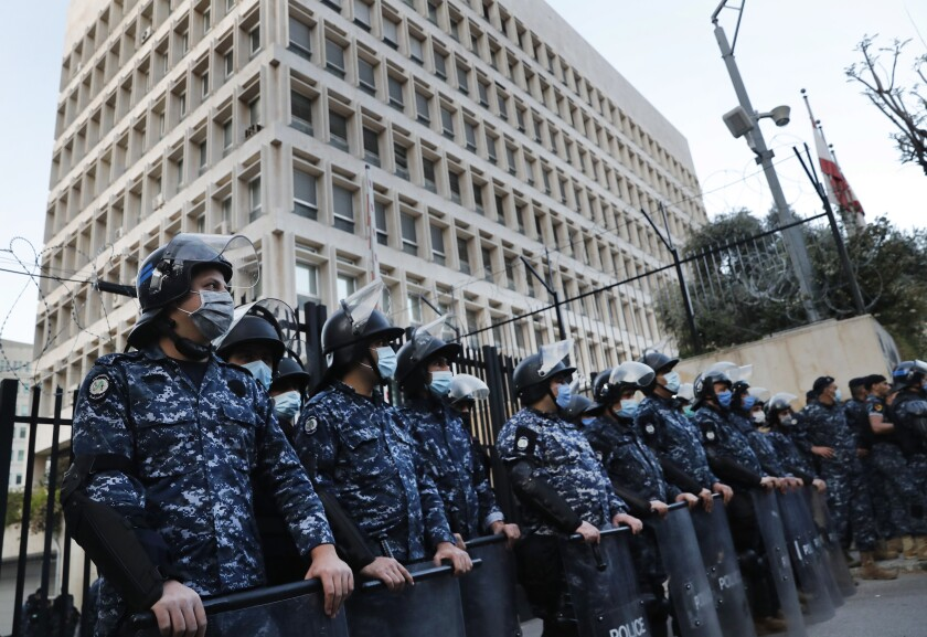 FILE - In this April 23, 2020, file photo, Lebanese riot police stand guard in front the central bank building, where the anti-government demonstrators protest against the Lebanese central bank's governor Riad Salameh and the deepening financial crisis, in Beirut, Lebanon. Lebanon's incoming Finance Minister Youssef El Khalil signed a contract on Friday, Sept. 17, 2021 with a New-York-based company, Alvarez & Marsal, to conduct a forensic audit of the country's central bank, a key demand of the international community to restore confidence in the crisis-struck country. (AP Photo/Hussein Malla, File)