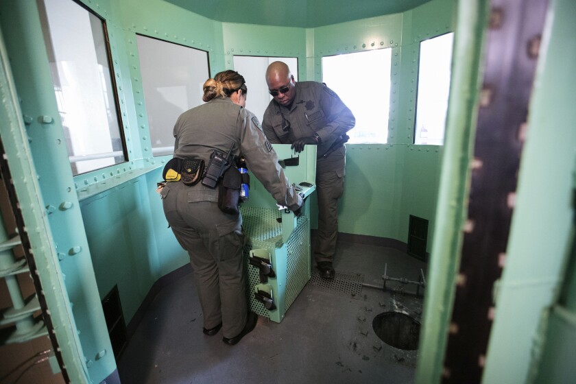 Two uniformed officers remove a green chair in a room with windows