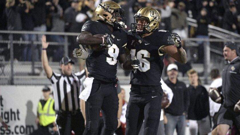 Central Florida running back Adrian Killins Jr. (9) is congratulated by wide receiver Tre Nixon (16)