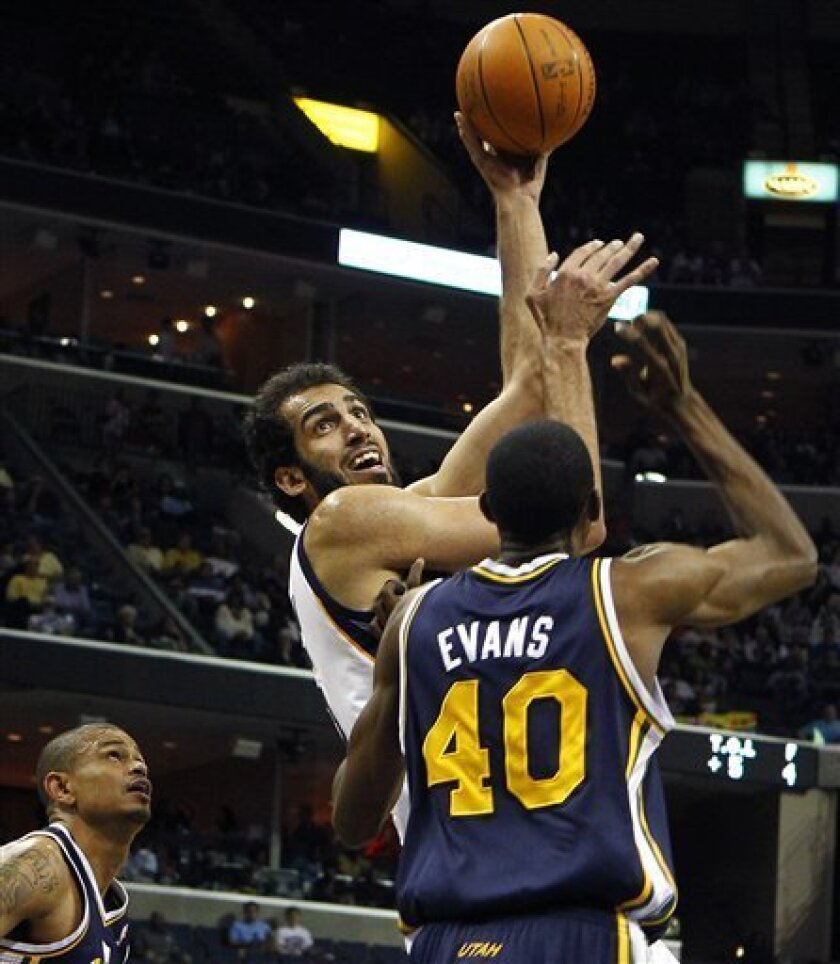 Memphis Grizzlies' Hamed Haddadi, top, of Iran, puts a shot over Utah Jazz's Jeremy Evans (40) as Earl Watson, left, looks on during the first half of a NBA basketball game in Memphis, Tenn., Monday, March 21, 2011. (AP Photo/ Mark Weber)