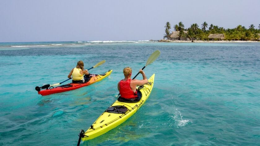 Young couple sea kayaking near Slickrock Adventures' Long Caye, Glover's Reef atoll, Belize.