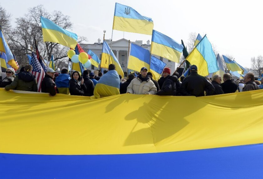 Demonstrators hold a large national flag of Ukraine during a rally to support Ukraine and denounce Russia outside the White House on Thursday. President Obama has said that a proposed referendum in Crimea would violate the Ukrainian constitution and international law.