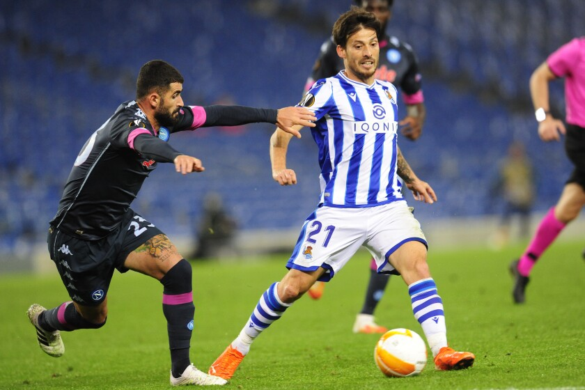 Real Sociedad's David Silva, right, vies for the ball with Napoli's Elseid Hysaj during the Europa League group F soccer match between Real Sociedad and Napoli at the Anoeta stadium in San Sebastian, Spain, Thursday, Oct. 29, 2020. (AP Photo/Amaia Zabalo)