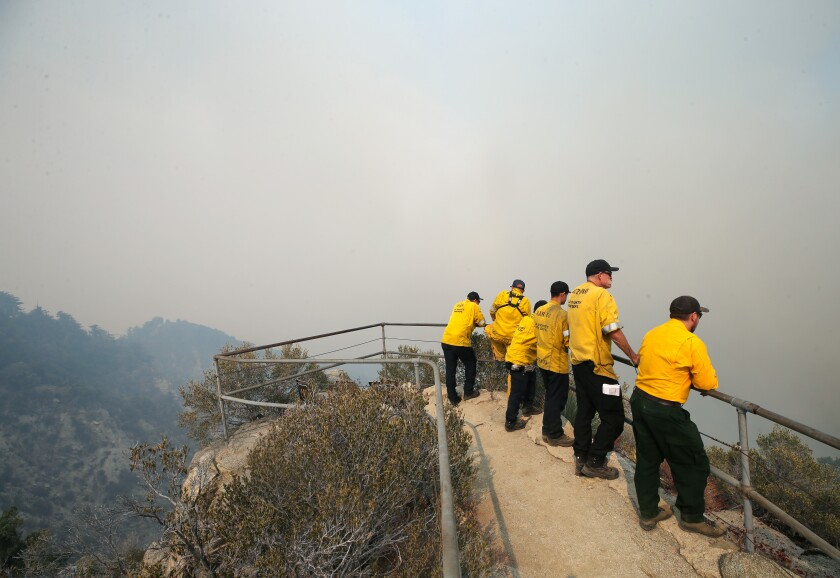 Firefighters keep watch from an overlook on Mount Wilson as the Bobcat Fire burns in the Angeles National Forest.
