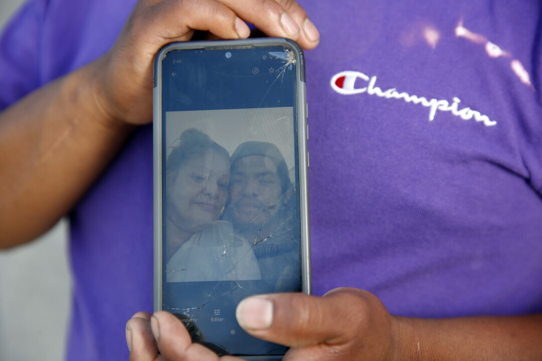 Close-up of a man holding a cellphone with a photo of him and his partner on it