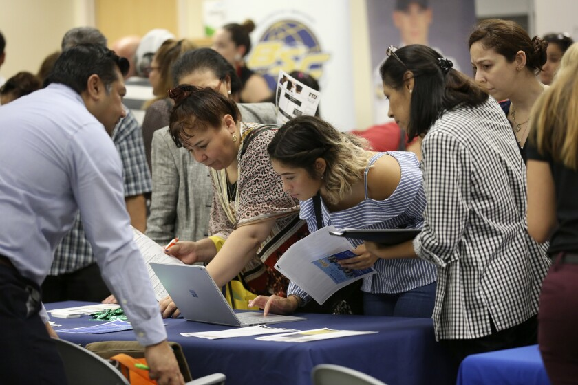 FILE - In this Sept. 18, 2019, file photo job applicants looks at jobs available at Florida International University during a job fair in Miami. On Wednesday, Jan. 8, 2020, payroll processor ADP reports on how many jobs its survey estimates U.S. companies added in December. (AP Photo/Lynne Sladky, File)