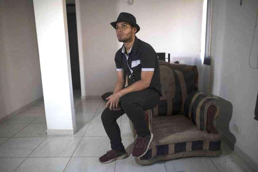 El migrante venezolano Alexander Beja en uno de los sofás de su apartamento en Ciudad Verde, Bogotá, Colombia. El cantautor mexicano Mario Domm del dúo pop Camila quedó cautivado con la voz de Beja.