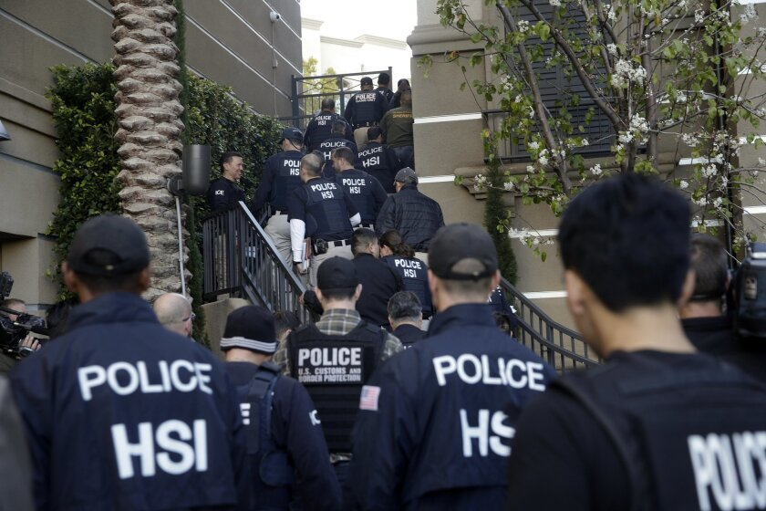 Federal agents enter an upscale apartment complex, Tuesday, March 3, 2015, in Irvine, Calif. Shortly after sunrise, federal agents swarmed the complex in the Orange County where authorities say a birth tourism business charged pregnant women $50,000 for lodging, food and transportation. The key dra