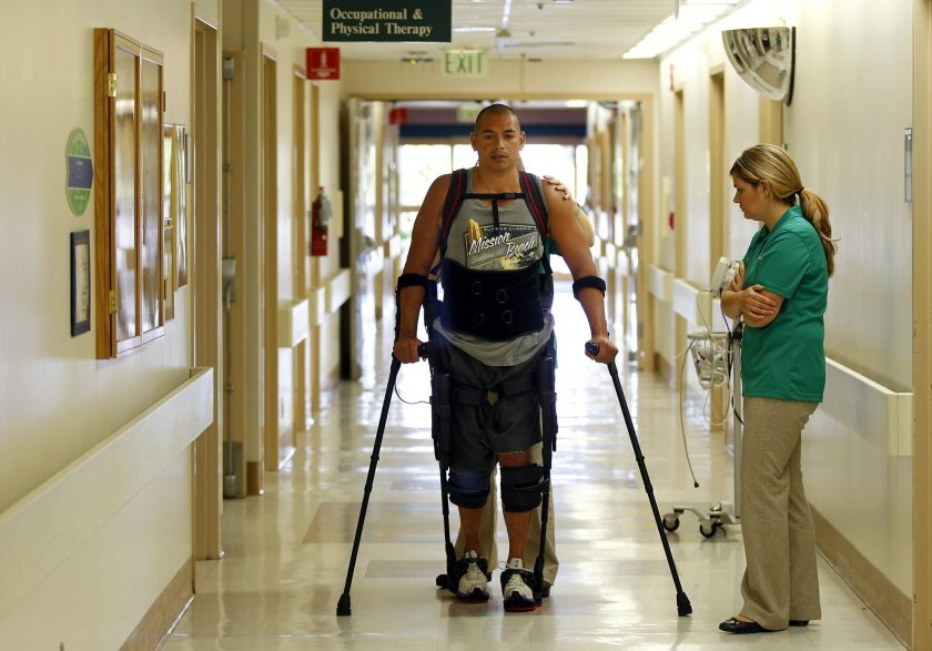 Hermes Castro walks with a help of an Ekso Bionics exoskeleton at Scripps Memorial Hospital Encinitas. Physical therapist Alyson Cavanaugh monitors Castro and the device. The exoskeleton is the first one in the county. Castro is a paraplegic patient who was hit by a vehicle while riding his bicycle.