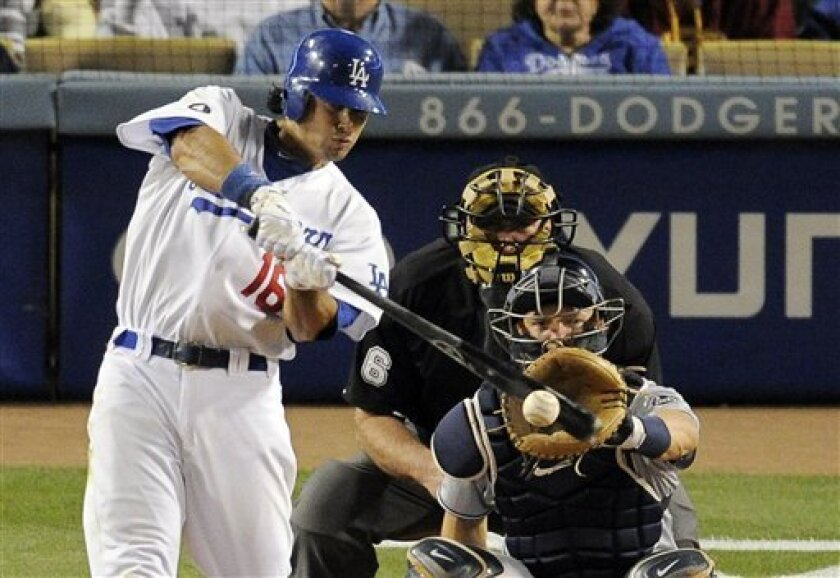 Los Angeles Dodgers' Andre Ethier, left, hits a single as San Diego Padres catcher Nick Hundley, lower right, and home plate umpire bob Davidson looks on during the eighth inning of their Major League Baseball game, Saturday, April 30, 2011, in Los Angeles. (AP Photo/Mark J. Terrill)