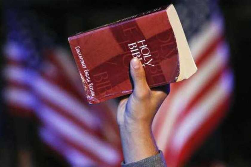 A hand holds a bible
