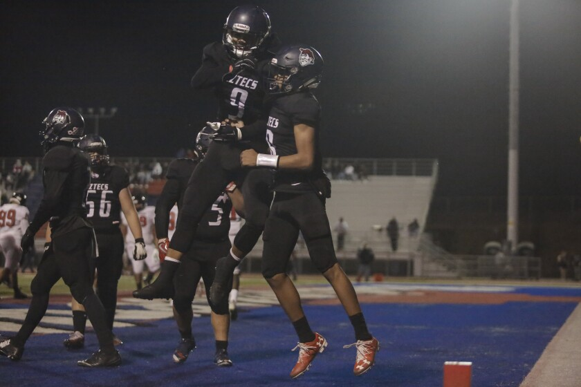 Montgomery quarterback Alexander Dixie celebrates an early touchdown run with Keoa Gumataotao (9), who later replaced an injured Dixie and sparked the Aztecs to the win.