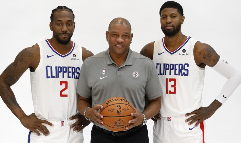 Clippers stars Kawhi Leonard, left, and Paul George pose with coach Doc Rivers for photos during the team's media day Sunday.