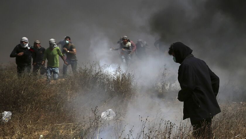 Palestinian protesters run from tear gas fired by Israeli troops after they burned tires during a protest at the Gaza Strip's border with Israel on Friday.