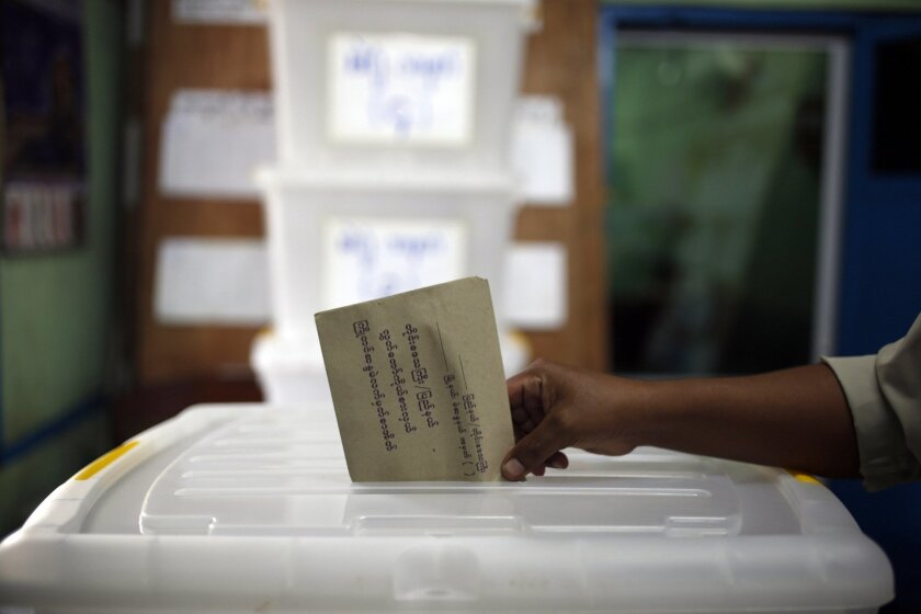 FILE - In this Friday, Oct. 30, 2015, file photo, a man casts his ballot in advance of the upcoming Nov. 8 general election at a township Election Commission Office in Mandalay, Myanmar. Myanmar will hold general elections on Sunday to choose representatives for both houses of Parliament, known as