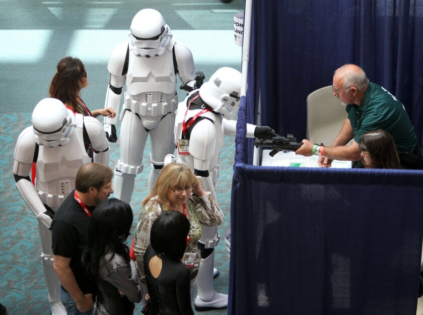 A few Stormtroopers get their weapons checked at a security desk at the entrance to Comic-Con. Sean M. Haffey • U-T file photo
