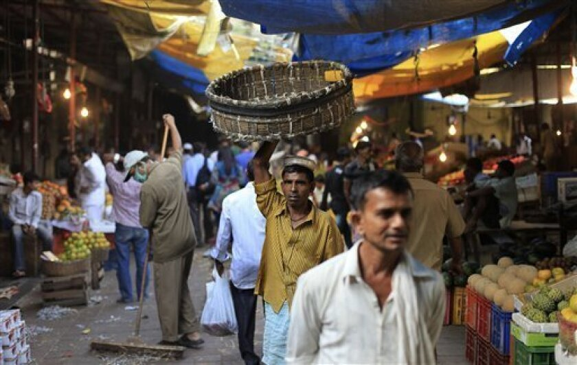 In this Saturday, Nov. 26, 2011 photo, a porter holds up his basket and makes his way through a crowded market in Mumbai, India. The arrival of modern retailing would hasten a cultural transformation in the way Indians shop and work. The debate now raging, which has shut down Parliament and may rip apart the ruling coalition, hinges on competing visions of what foreign retailers will bring for India's two largest sources of jobs: agriculture and retail. The existing retail landscape is an intricately evolved tangle of shops and bazaars, which has been forged by ideas that date back to India's earliest religious texts. (AP Photo/Rafiq Maqbool)