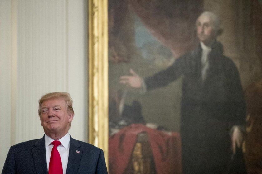 Donald Trump stands near a portrait of George Washington during a Wounded Warrior Project Soldier Ride event in the East Room of the White House, Thursday, April 18, 2019