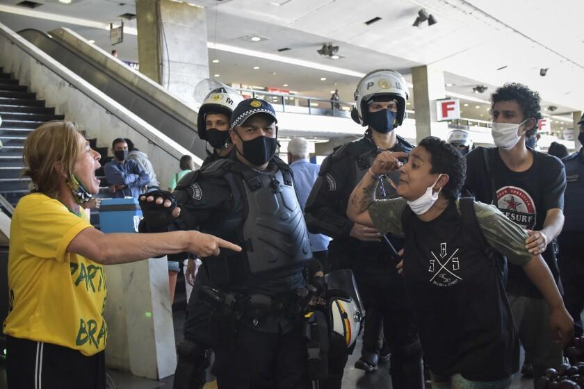 Oficiales de la policía militar brasileña separan a los manifestantes leales al presidente de Brasil.