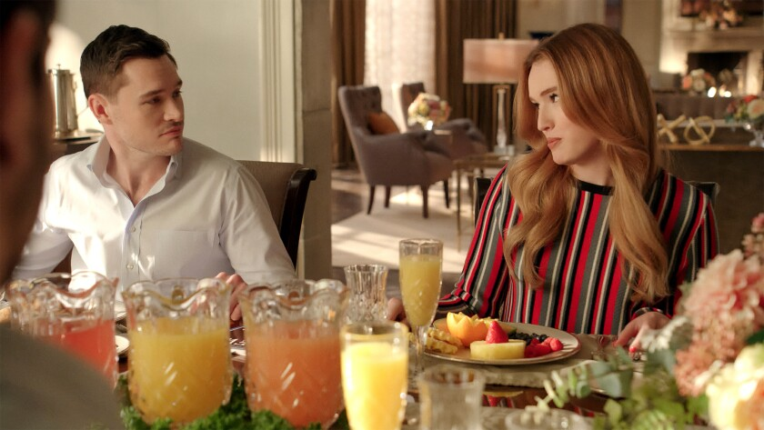 A man and a woman look at each other while sitting at a dining table.