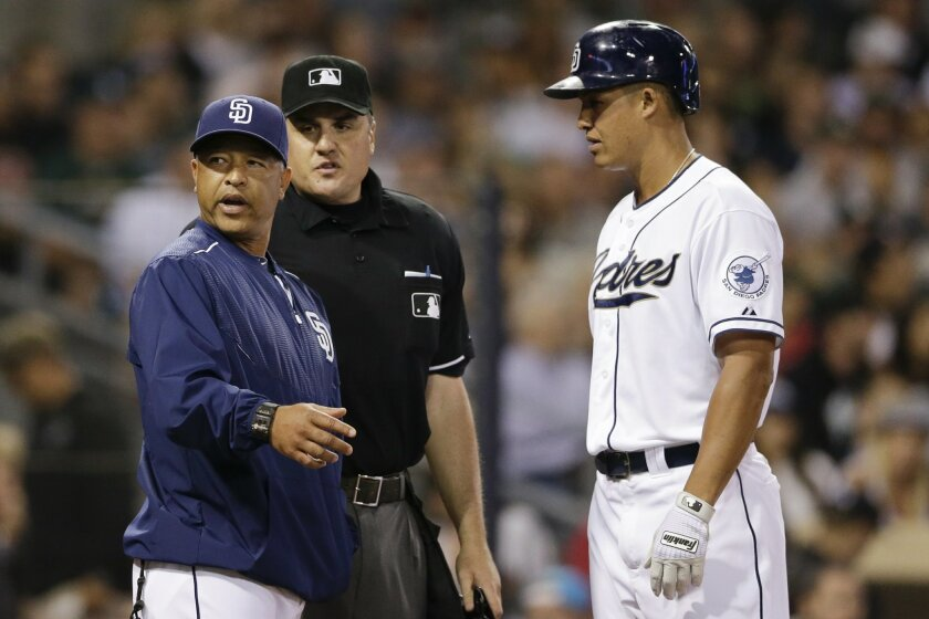 San Diego Padres acting manager Dave Roberts, left, discusses a play with umpire Mike DiMuro, center, as San Diego Padres' Will Venable looks on while playing the Oakland Athletics during the fourth inning of a baseball game Monday, June 15, 2015, in San Diego. (AP Photo/Gregory Bull)