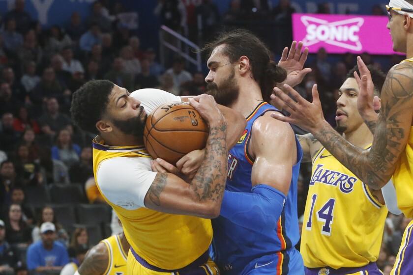 Lakers forward Anthony Davis battles Thunder center Steven Adams for the ball Nov. 22, 2019.