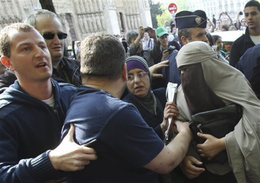 An unidentified veiled woman, right, is taken away by plain clothed police officers, left and second left, as she is accompanied by two friends, cente left and right, in Paris Monday, April 11, 2011. France's new ban on Islamic face veils was met with a burst of defiance Monday, as several women appeared veiled in front of Paris' Notre Dame Cathedral and two were detained for taking part in an unauthorized protest. France on Monday became the world's first country to ban the veils anywhere in public. (AP Photo/Michel Euler)