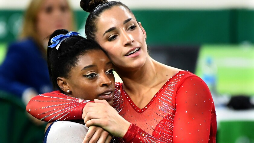 Simone Biles, left, and Aly Raisman embrace after clinching their gold and silver medals in the women's gymnastics all-around event Thursday.