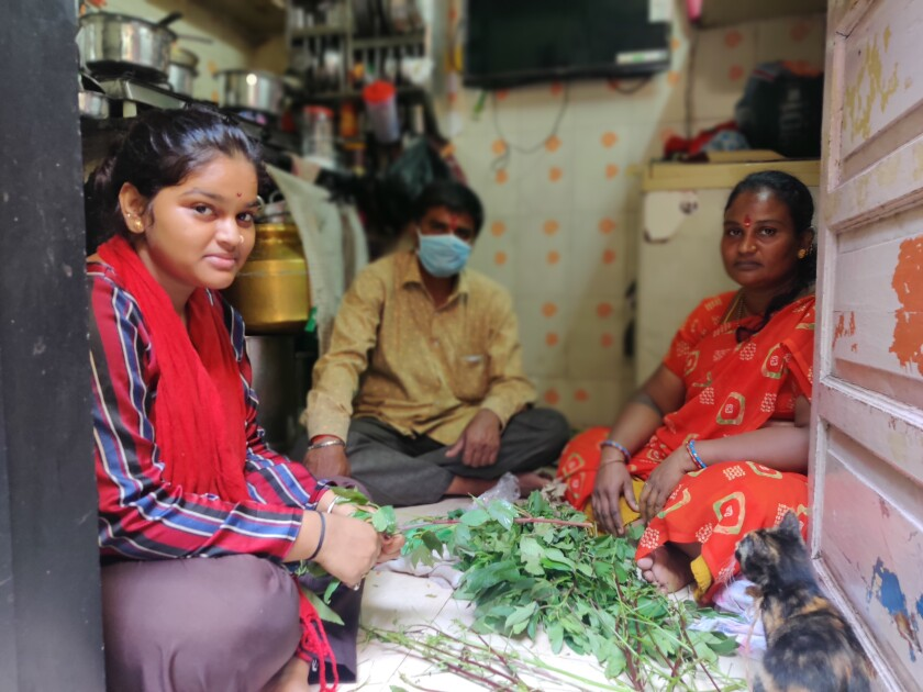 Vishakha, left, Ashok and Renuka Kunchikurve are pictured in their one-room house in Dharavi, a slum in Mumbai, India.