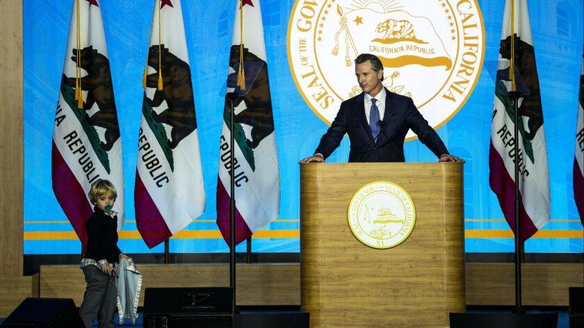 SACRAMENTO, CALIF. - JANUARY 07: California Governor Gavin Newsom speaks while his youngest son, Dut