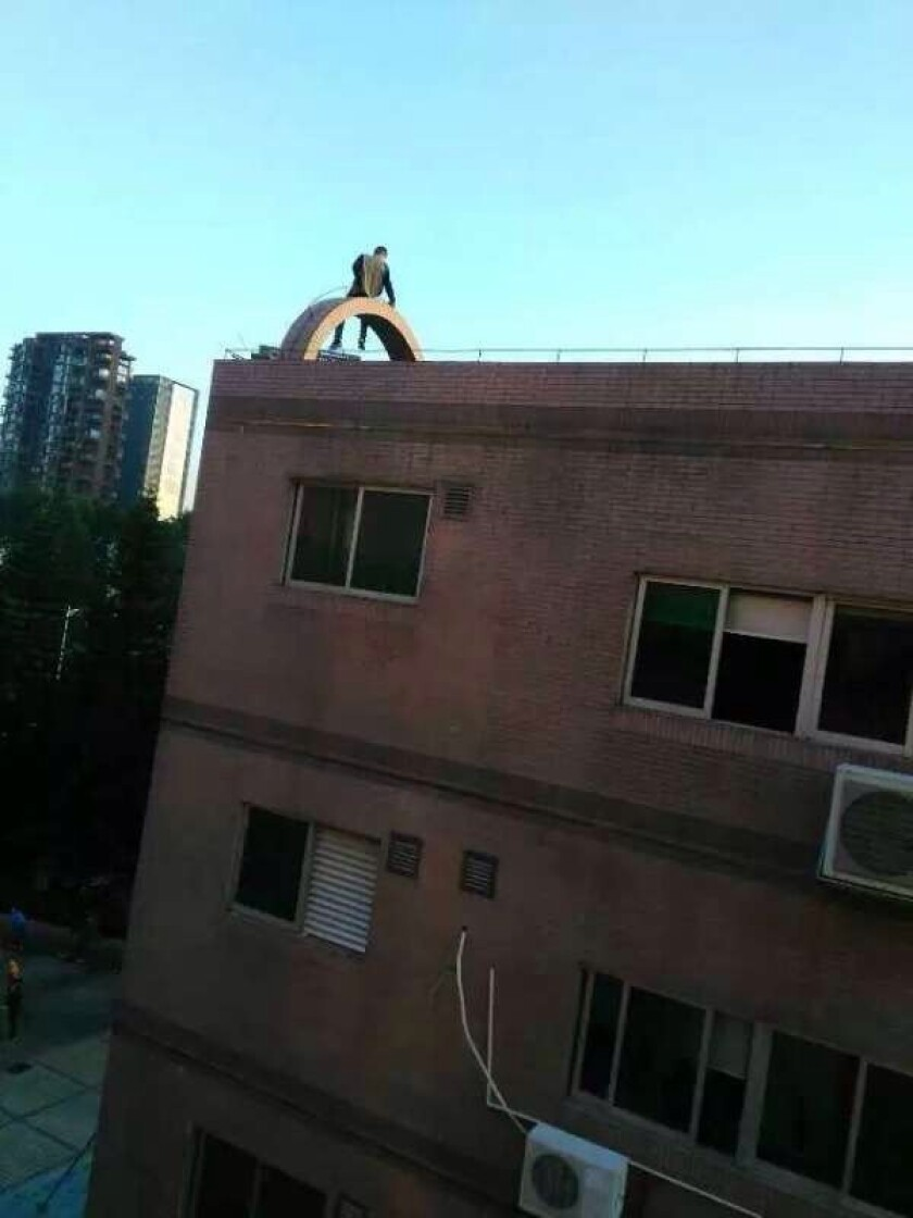 An employee of G. Credit factory in Shenzhen, China contemplates suicide after the company informed employees they wouldn't receive wages as scheduled.