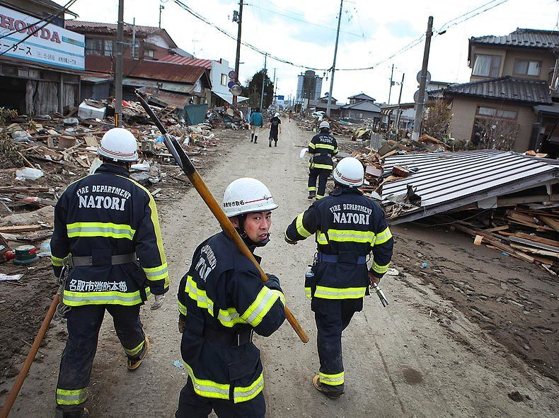 Firefighters patrol the streets of Natori, where hundreds of homes were swept away.