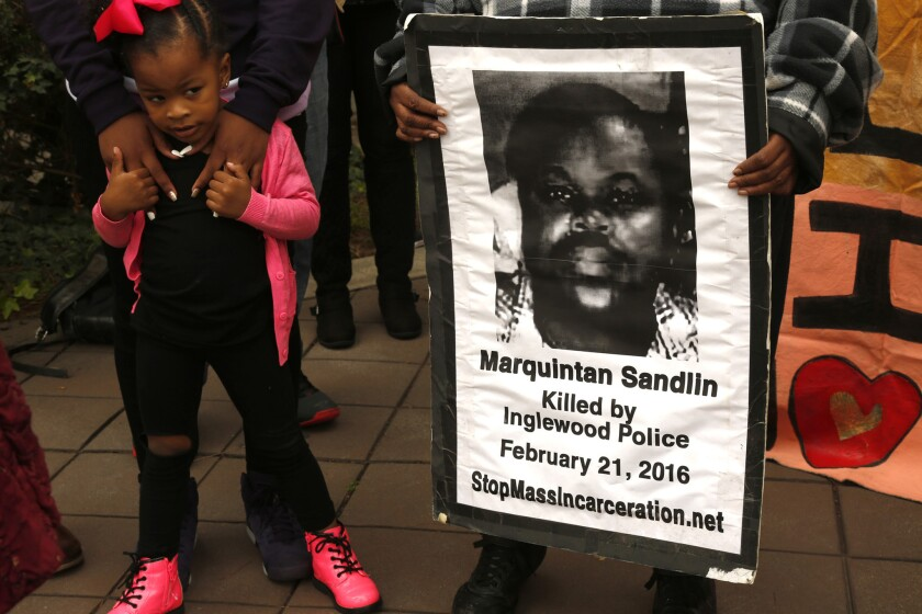 Kylia Fields, 3, stands next to a poster of her cousin as family and community members rally to demand more information in the deaths of Kisha Michael and Marquintan Sandlin in front of City Hall in Inglewood on Feb. 21. Inglewood police officers shot and killed the couple a year ago to the day.