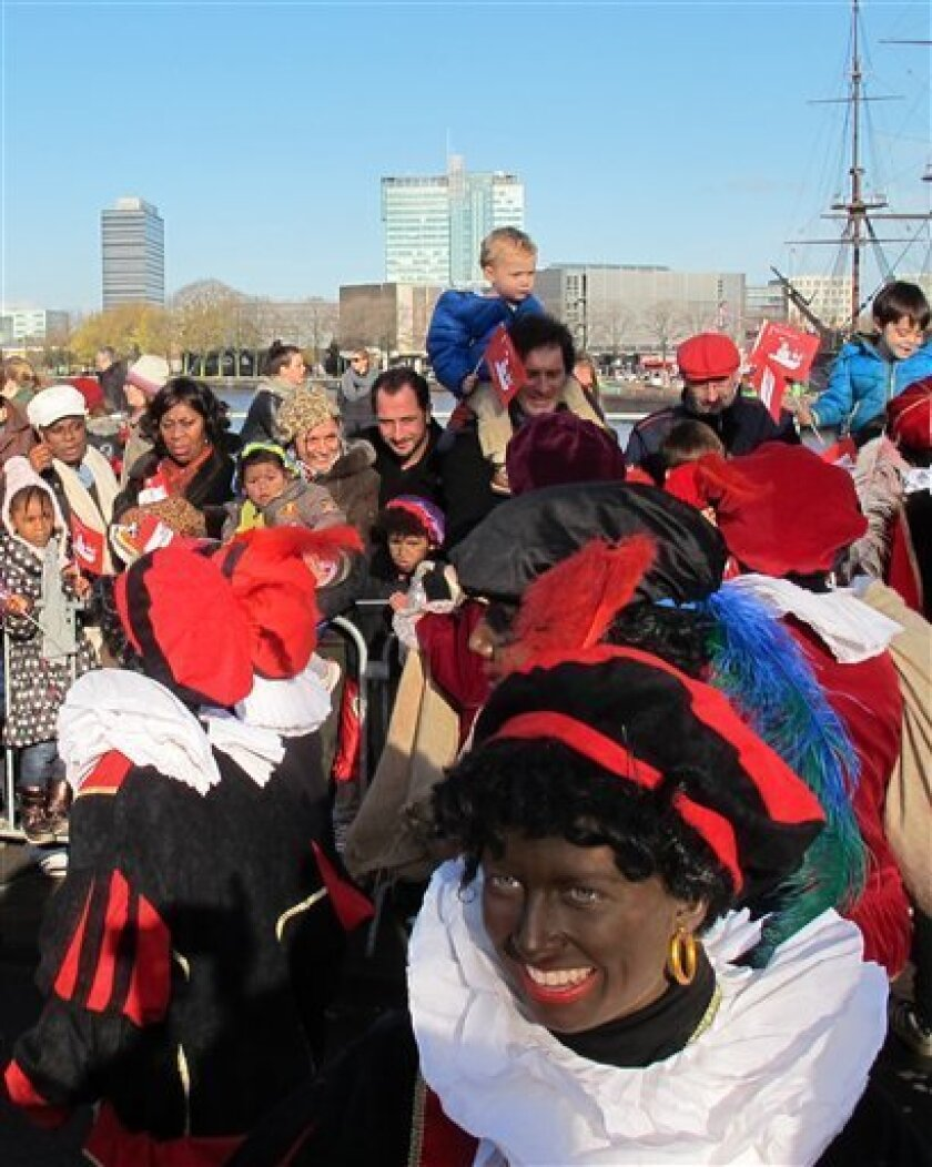 "In this photo taken Sunday, Nov. 18, 2012 persons dressed as ""Zwarte Piet"" or ""Black Pete"" attend a parade after St. Nicholas, or Sinterklaas, arrived by boat in Amsterdam, Netherlands. Foreigners visiting the Netherlands in winter are often surprised to see that the Dutch version of St. Nicholas' little helpers resemble a racist caricature of a black person. The overwhelming majority of Dutch, who pride themselves on tolerance, are fiercely devoted to their holiday tradition and say ""Zwarte Piet"", whose name means ""Black Pete"", is absolutely harmless, a fictional figure who does not represent any race. But now a growing group of Dutch natives are questioning whether this particular part of the tradition should be changed. (AP Photo/ Margriet Faber)"