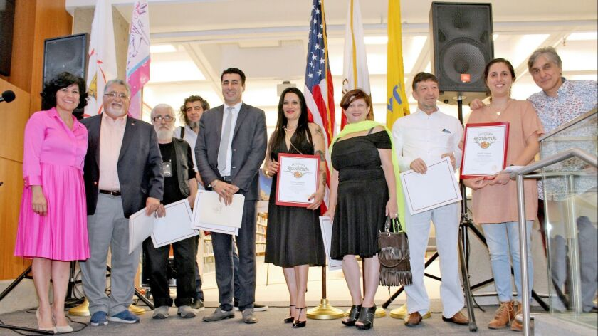 """Yerevan 2800"" co-curator Ara Oshagan, left, and state Sen. Anthony Portantino next to her pose with the exhibit's artists, all of which received a State Senate Certificate of Recognition."