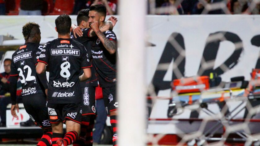The Xolos celebrate a goal Friday night against Atlas.