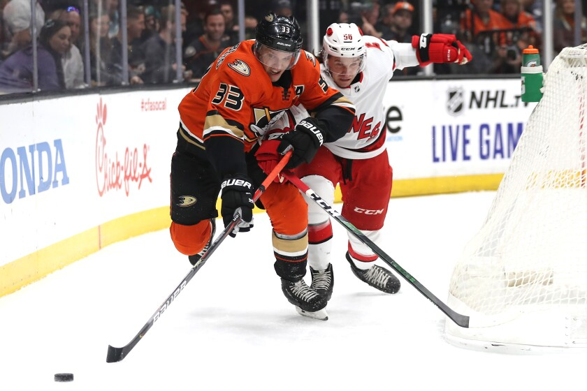 The Ducks' Jakob Silfverberg battles the Hurricanes' Erik Haula for a loose puck during the first period at Honda Center on Oct. 18.