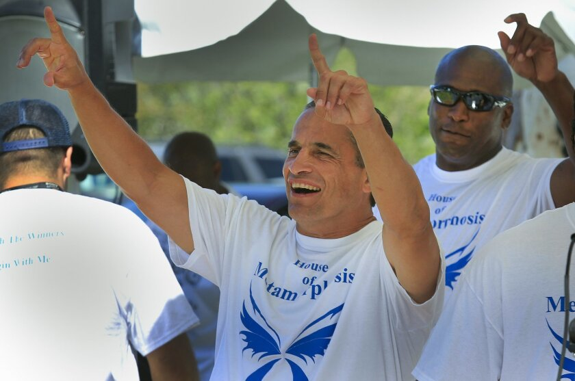 """Mike Zena joins fellow members of the House of Metamorphosis Choir to sing """"Lean on Me"""" during the Recovery Happens resource fair at Balboa Park."""
