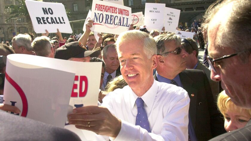 Then-California Gov. Gray Davis autographs picket signs during a campaign stop in San Francisco in October 2003, just before voters recalled him from office.