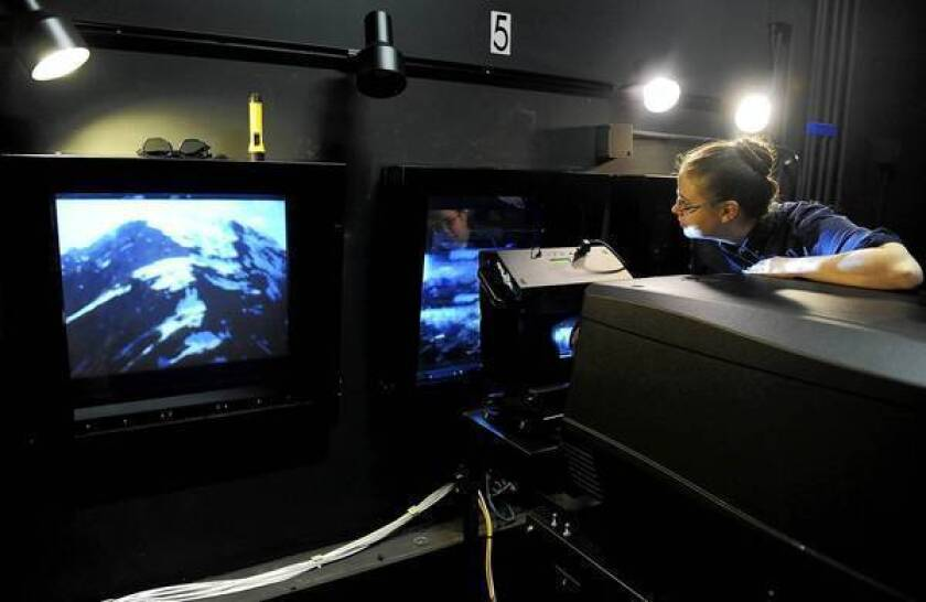 """Erica Lange works the projector at the Landmark theater in West L.A., where Warner Bros. ran a test reel of """"The Hobbit: An Unexpected Journey."""" It's the first major release shot at 48 frames a second."""