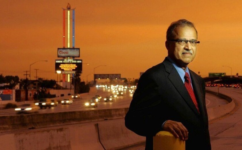Pervaiz Lodhie, who owns an LED lighting business in Torrance, stands along the 110 Freeway near the Los Angeles Memorial Coliseum & Sports Arena sign. He decided that the sign's burned-out and flickering fluorescent tubes needed to be replaced, and then donated the new bulbs himself.