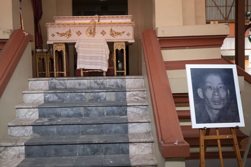 A portrait of the infamous serial killer Si Ouey is displayed below his coffin ahead of the cremation of his remains.