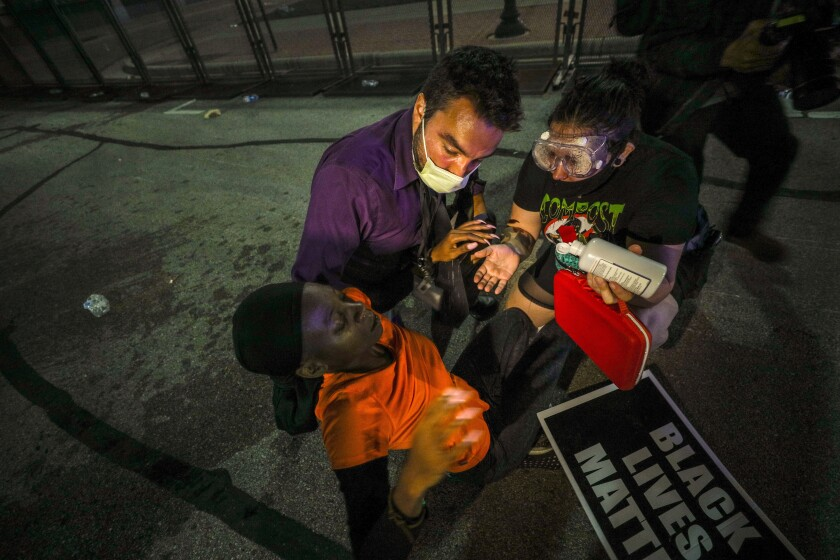 Protesters help a man during demonstrations  over the shooting  in Kenosha